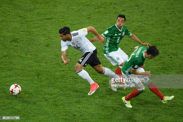 Emre Can of Germany goes past Marco Fabian and Hector Herrera of Mexico during the FIFA Confederations Cup Russia 2017 SemiFinal between Germany and...