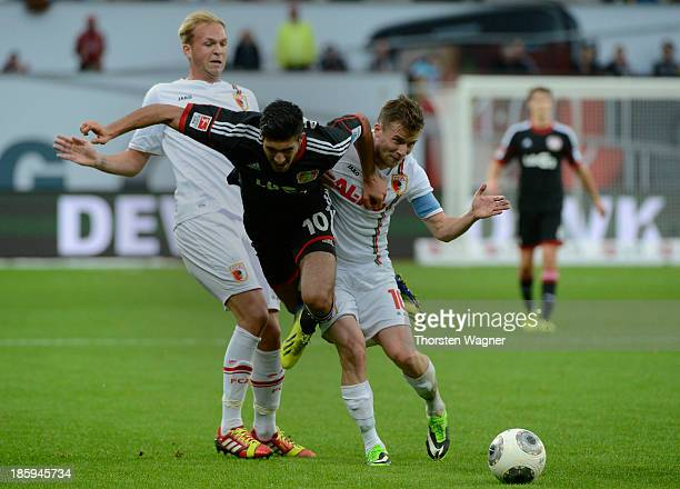 Emre Can of Leverkusen battles for the ball with Raphael Holzhauser and Daniel Baier of Augsburg during the Bundesliga match between Bayer 04...
