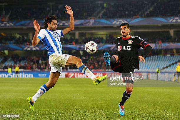 Emre Can of Leverkusen is challenged by Carlos Martinez of Real Sociedad during the UEFA Champions League Group A match between Real Sociedad de...