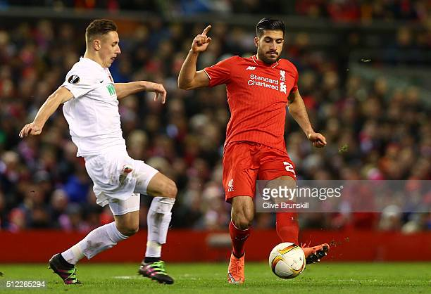 Emre Can of Liverpool and Dominik Kohr of Augsburg compete for the ball during the UEFA Europa League Round of 32 second leg match between Liverpool...