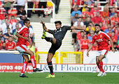 Emre Can of Liverpool competes with James Dayton of Swindon Town during a preseason friendly at County Ground on August 2 2015 in Swindon England