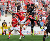 Emre Can of Liverpool goes up with Nathan Byrne of Swindon Town during a preseason friendly at County Ground on August 2 2015 in Swindon England