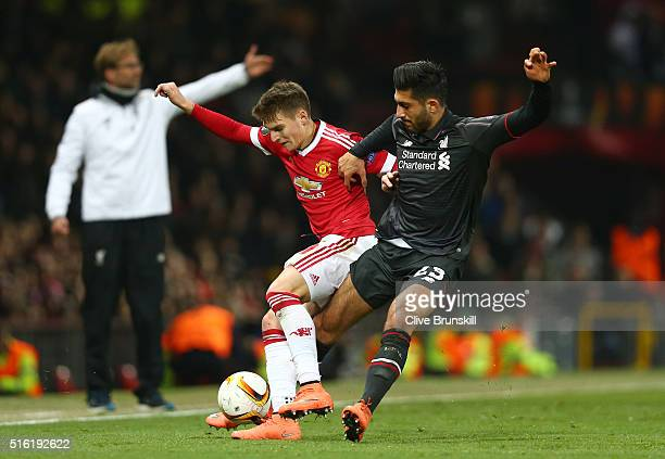 Emre Can of Liverpool tussles with Guillermo Varela of Manchester United during the UEFA Europa League round of 16 second leg match between...