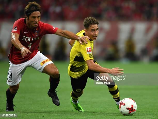 Emre Mor of Burussia Dortmund and Daisuke Nasu of Urawa Red Diamonds compete for the ball during the preseason friendly match between Urawa Red...