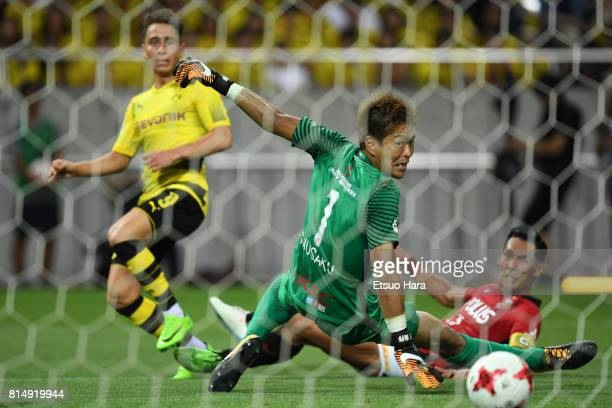 Emre Mor of Burussia Dortmund scores his side's first goal past goalkeeper Shusaku Nishikawa of Urawa Red Diamonds during the preseason friendly...