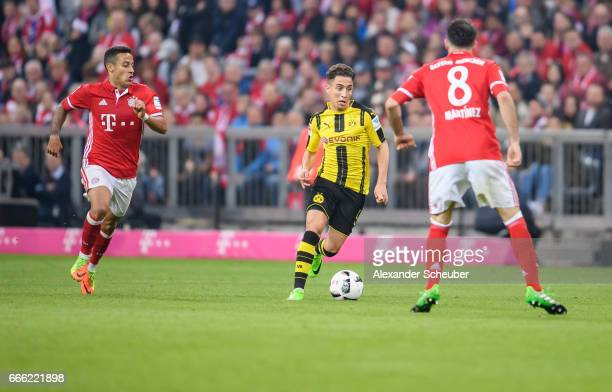 Emre Mor of Dortmund in aciton against Thiago of Bayern Muenchen and Javi Martinez of Bayern Muenchen during the Bundesliga match between Bayern...