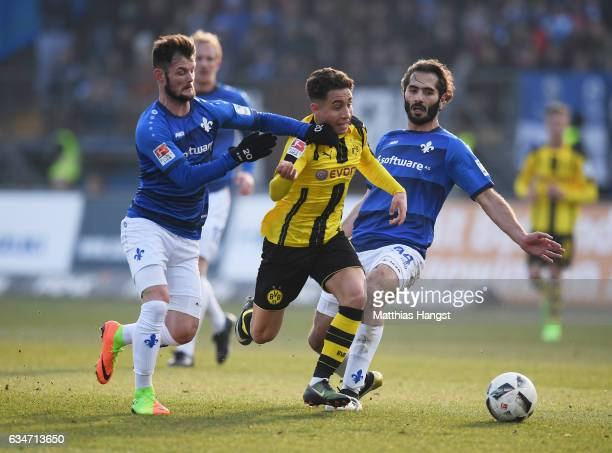 Emre Mor of Dortmund is challenged by Marcel Heller of Darmstadt and Hamit Altintop of Darmstadt during the Bundesliga match between SV Darmstadt 98...