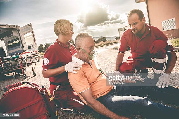EMTs on street giving man first aid