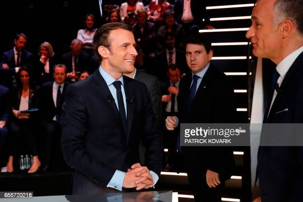 En Marche movement Emmanuel Macron speaks with journalist Gilles Bouleau before taking part in a debate between five candidates for the French...