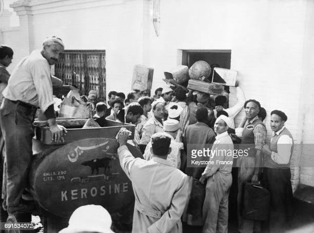 En raison de la pénurie d'essence pendant la crise de Suez un groupe d'égyptiens faisant la queue devant un commerce de kérosène utilisé pour leur...