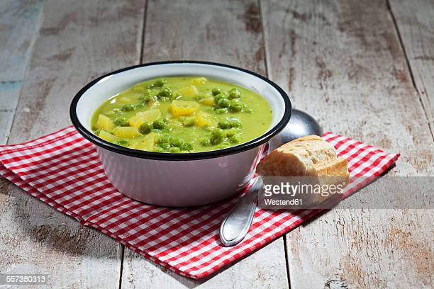 Enamel bowl of pea stew, spoon and sliced baguette on cloth and wood