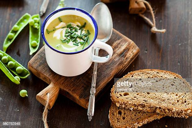 Enamel cup of pea soup with chives and slices of bread