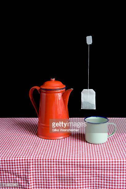 Enamel teapot and cup on table with teabag floating mid-air