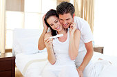 Enamored couple finding out results of a pregnancy test sitting on the bed