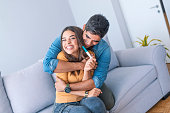 Enamoured couple finding out results of a pregnancy test sitting on the bed. Happy couple checking pregnancy test sitting on a couch in the living room at home. Family, parenting and medical concept