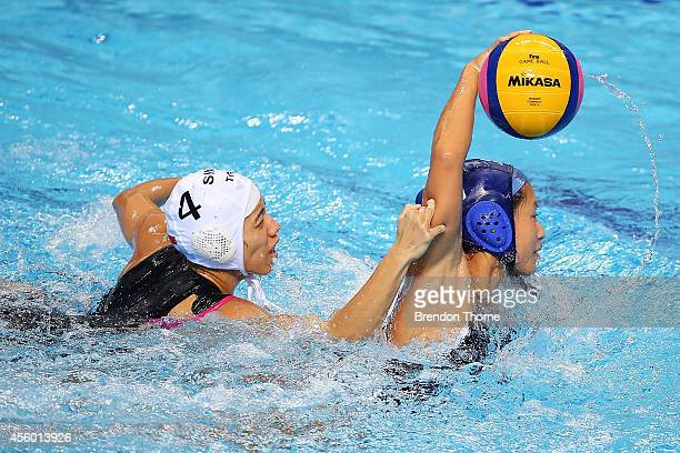 Enci Mary Kan of Singapore competes with Yumi Kojo of Japan in the Women's Single Round Robin Waterpolo during day five of the 2014 Asian Games at...