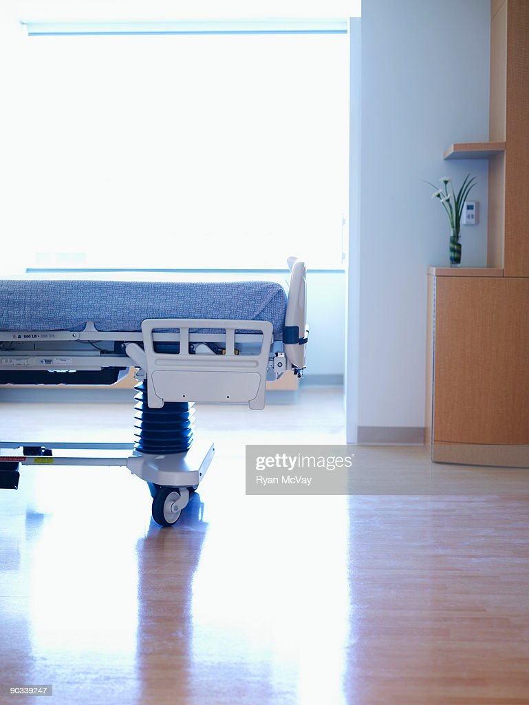 end of hospital bed in empty hospital room