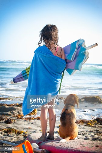 end of the day at the beach, a girl and her dog : Stock Photo