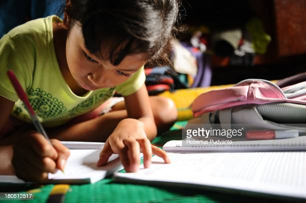 Endang the youngest known traditional ulos weaver completes her studies as a junior high school student on September 14 2013 in Samosir North Sumatra...