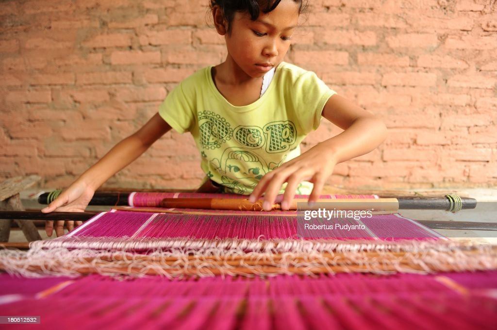 Endang, the youngest known traditional ulos weaver, makes an ulos on a loom on September 14, 2013 in Samosir, North Sumatra, Indonesia. Endang Ernawati Simanihuruk, aged 11, is the youngest known traditional ulos (traditional cloth shawl) weaver working in Samosir Island, North Sumatra. Endang was born and raised in the Simarmata village of Simanindo, Samosir Regency, and began weaving at 8 years old to contribute to her parent's income. Endang weaves every day after school and earns roughly $8 from a single ulos, approximately a week's work. Today it is very difficult to find young people who want to continue the profession as a traditional ulos weaver because of the competition from factory-made weaving machines.