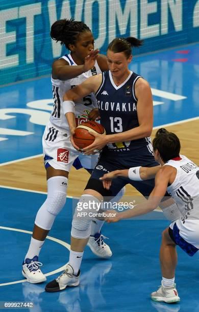 Endene Miyem and Celine Dumerc both of France try to block Anna Jurcenkova of Slovakia during the FIBA EuroBasket women's quarterfinal match between...