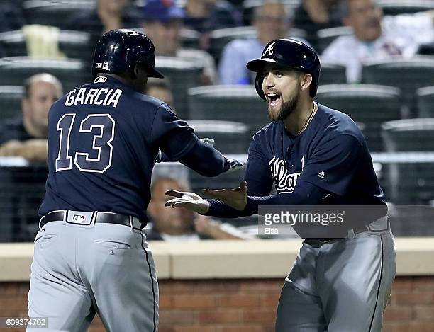 Ender Inciarte of the Atlanta Braves congratulates teammate Adonis Garcia after Garcia hit a three run home run in the seventh inning against the New...