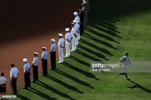 Ender Inciarte of the Atlanta Braves runs past members of the military prior to a game against the Los Angeles Angels of Anaheim during the inning of...