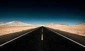 Endless Straight Road through Desert Mountains
