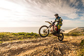 Enduro rider climbing a steep slope against a beautiful sunset on a seascape