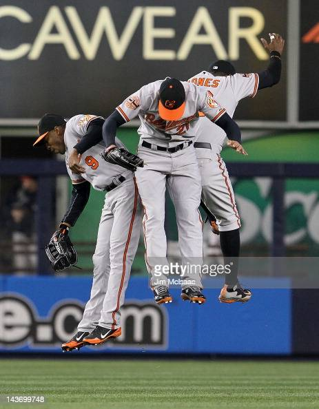 Endy Chavez Nick Markakis and Adam Jones of the Baltimore Orioles celebrate after defeating the New York Yankees at Yankee Stadium on May 2 2012 in...