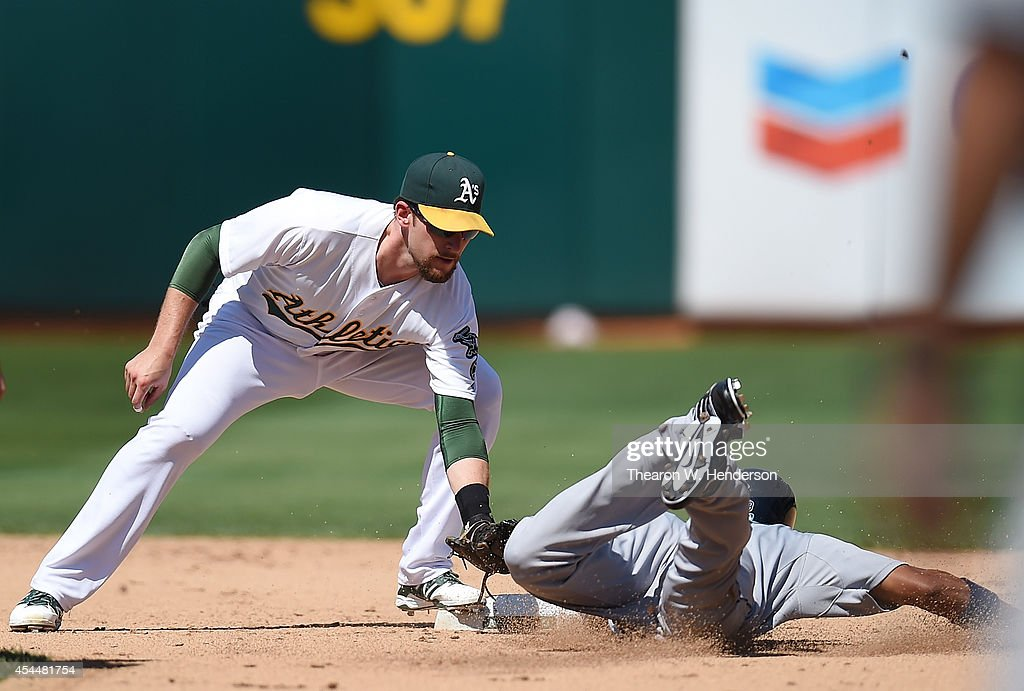 <a gi-track='captionPersonalityLinkClicked' href=/galleries/search?phrase=Endy+Chavez&family=editorial&specificpeople=216624 ng-click='$event.stopPropagation()'>Endy Chavez</a> #9 of the Seattle Mariners gets caught stealing second base by <a gi-track='captionPersonalityLinkClicked' href=/galleries/search?phrase=Jed+Lowrie&family=editorial&specificpeople=4949369 ng-click='$event.stopPropagation()'>Jed Lowrie</a> #8 of the Oakland Athletics in the top of the fifth inning at O.co Coliseum on September 1, 2014 in Oakland, California.