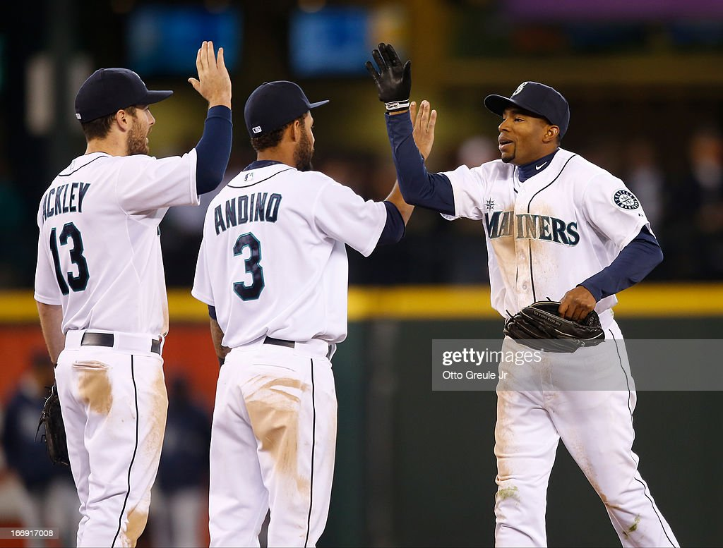 Endy Chavez #9 (R) of the Seattle Mariners is congratulated by Dustin Ackley #13 and Robert Andino #3 after defeating the Detroit Tigers 2-0 at Safeco Field on April 18, 2013 in Seattle, Washington.