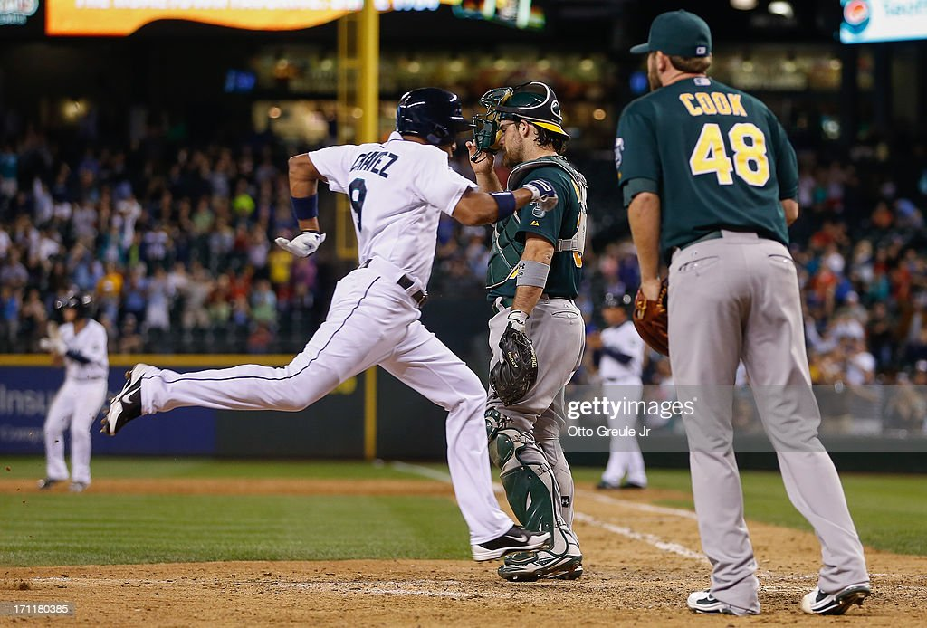 Endy Chavez #9 of the Seattle Mariners scores on an RBI single by Nick Franklin past catcher Derek Norris #36 and relief pitcher Ryan Cook #48 of the Oakland Athletics in the eighth inning at Safeco Field on June 22, 2013 in Seattle, Washington.