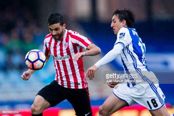 Eneko Boveda of Athletic Club Bilbao duels for the ball with Mikel Oyarzabal of Real Sociedad during the La Liga match between Real Sociedad de...