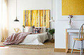 Energetic and warm bedroom with yellow artwork, plant and desk