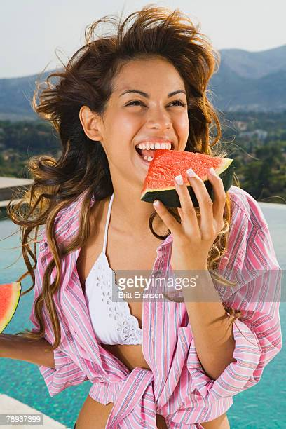 Energetic woman with smile eats watermelon by pool outside.