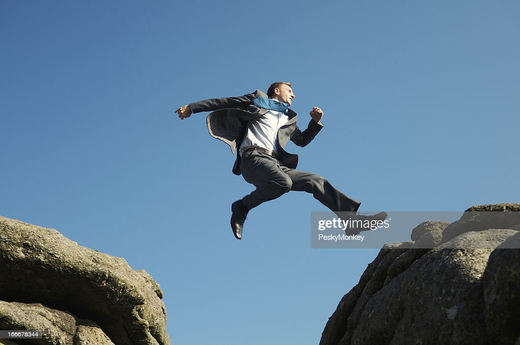 Energetic Young Man Businessman Jumping into Blue Sky between Rocks : Stock Photo
