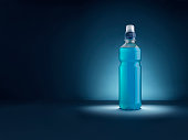Shot of an energy drink on a blue, vignette, spotlit style background with plenty of copy space for the designer. The spotlit has been achieved by lighting not post production adjustments.