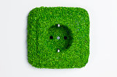 Energy saving electrical wall outlet covered in green grass