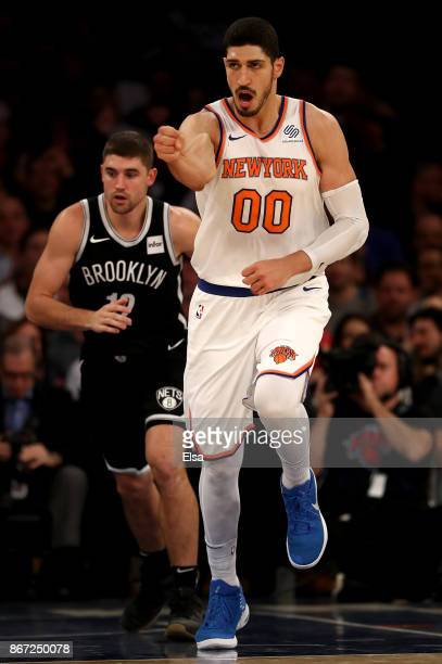 Enes Kanter of the New York Knicks celebrates his basket in the second half as Joe Harris of the Brooklyn Nets looks on at Madison Square Garden on...