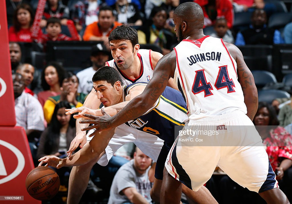 Enes Kanter #0 of the Utah Jazz loses the ball against Zaza Pachulia #27 and Ivan Johnson #44 of the Atlanta Hawks at Philips Arena on January 11, 2013 in Atlanta, Georgia.