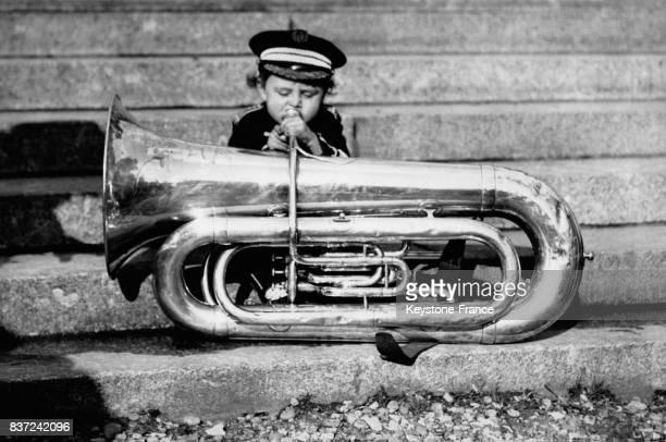 Enfant assis dans un escalier soufflant dans un tuba à Londres RoyaumeUni