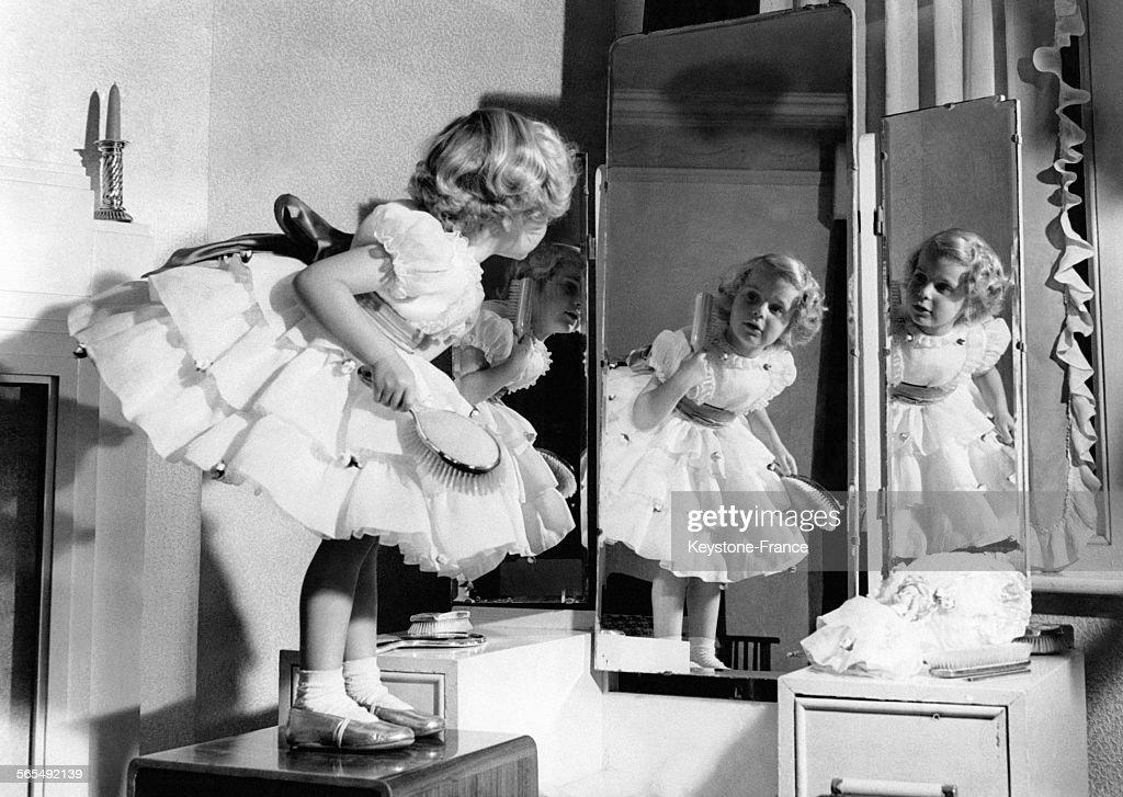 Enfant coquette, montée sur un meuble, vérifiant sa coiffure dans un miroir.