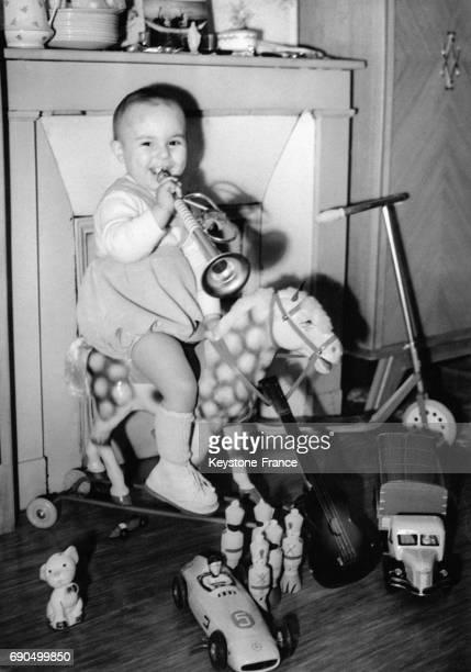 Enfant dans sa chambre entouré de jouet souffle dans une trompette