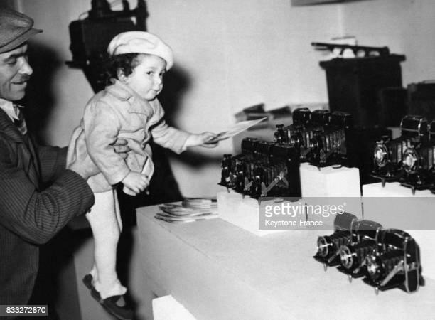 Enfant devant un stand d'appareils photo au salon de la photo à Paris France le 4 mars 1938