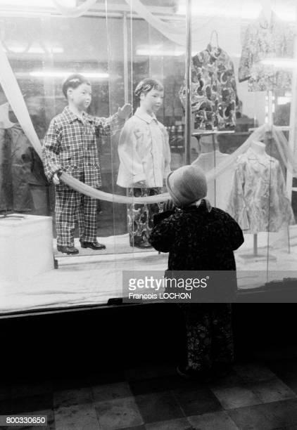 Enfant devant une vitrine d'un magasin à Canton en février 1979 en Chine