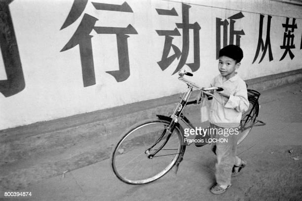 Enfant poussant un vélo et idéogrammes au second plan en décembre 1977 à Canton Chine