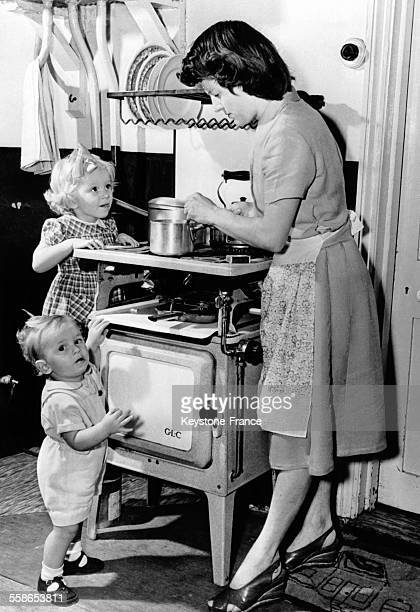 Enfants accroches a une cuisiniere a gaz en train d'observer leur mere qui cuisine circa 1940