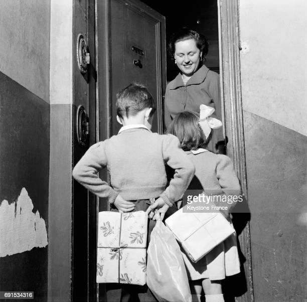 Enfants cachant des cadeaux dans leur dos pour les offir par surprise à leur maman à l'occasion de la nouvelle année en France le 29 décembre 1956