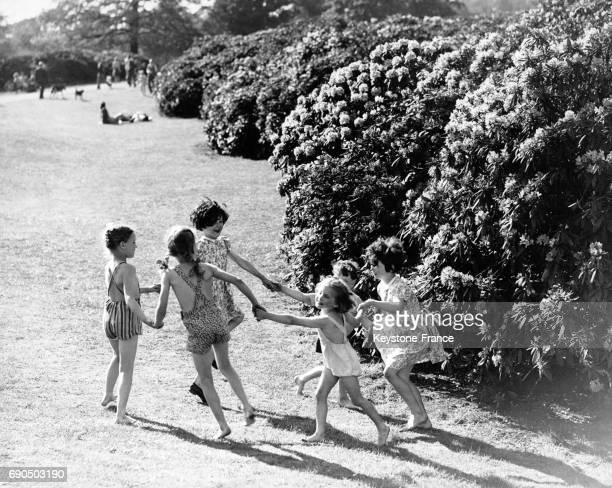Enfants faisant la ronde devant un buisson de rhododendrons en fleurs à Dulwich Park Londres RoyaumeUni le 19 mai 1948